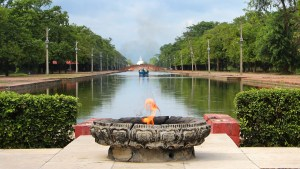 An eternal flame in Lumbini Development Zone with a body of water in the background.