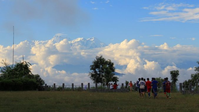 Children playing football in Tundikhel, Bandipur, Nepal with high Himalayan mountain rising in the background.
