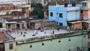 Young men playing cricket at a concrete rooftop in Khulna.