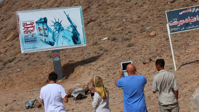 Things you miss when you travel. Tourists taking a photograph of an anti-American propaganda billboard by the side othe road in Iran.