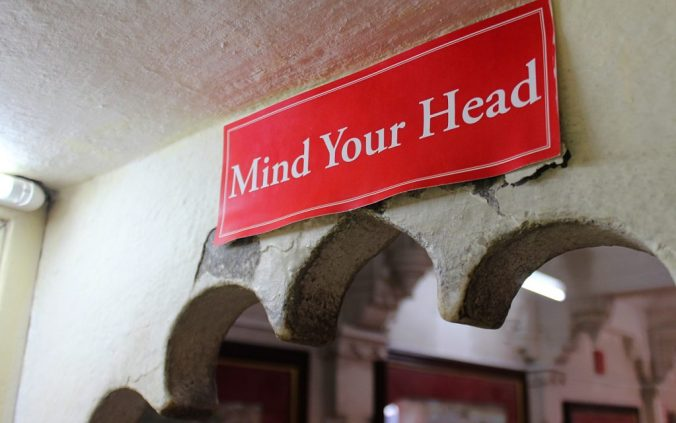 """The psychology of travel. A red sign saying """"mind your head"""" inside city palace, Udaipur."""