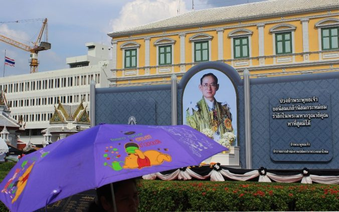 A woman holding a purple Winnie the Pooh umbrella in front of a King Bhumibol honour.