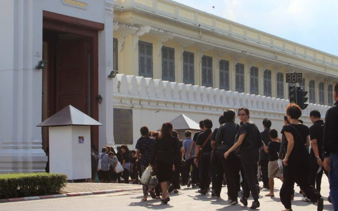 Mourners of the late king Bhumibol march to the Grand Palace in Bangkok, Thailand. All people are wearing either black or white.