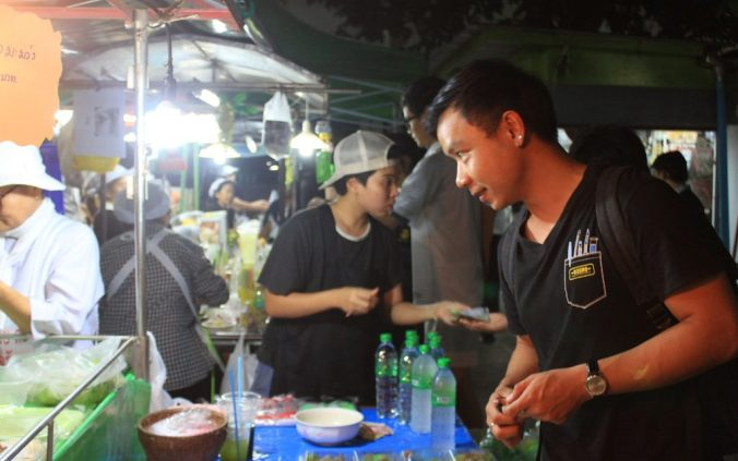 A Thai man buying fruits from a street vendor in front of the Kasetsart University canteen in Bangkok, Thailand.