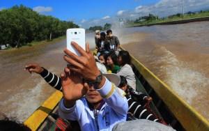 A guy from Myanmar taking selfie on a long boat in Inle Lake.