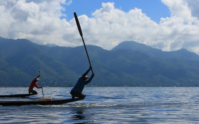 A local fisherman hitting water surface with a paddle in Inle Lake.