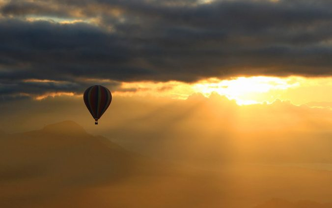 Hot air ballooning in Vang Vien, Laos. A hot air balloon flying against the sunrise in the background.