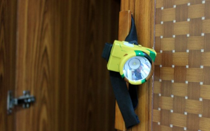 A headlamp from Laos hanging on the door of a hotel room drawer.