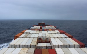Cargo ship travel. A cargo ship surrounded by grey clouds.