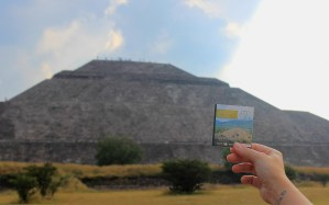 The Pyramid of the Sun in Teotihuacan. A hand holding an entrance ticket to Teotihuacan in front of the pyramid.