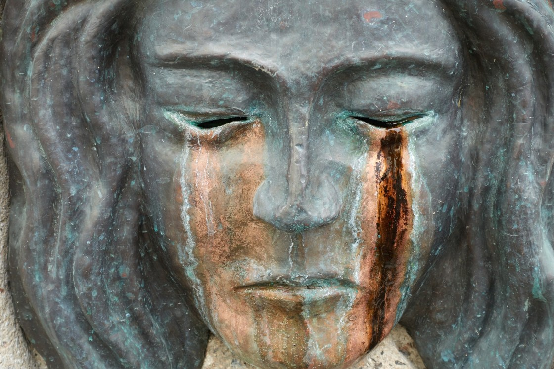 Face of crying bronze statue