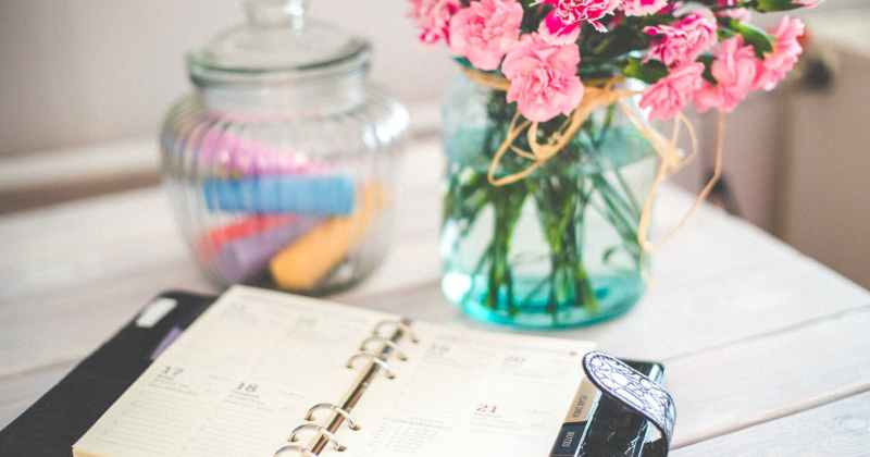 Daily planner book on table with flowers