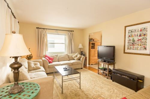 A bright colored living room complete with sofas and television set. Windows are lined with curtains for daytime use.