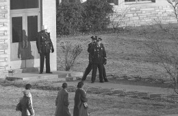 Three police officers stand at the entrance to Stratford Jr. High School as the four black students enrolled in the previously all-white school arrive for classes in Arlington, Va., on Feb. 3, 1959.  One of the officers records the scene with a movie camera.  Approaching the entrance are, left to right, Lance Newman, 13, Ronald Deskins, 12, Michael Jones, 12, and Gloria Thompson, 12.  (AP Photo)