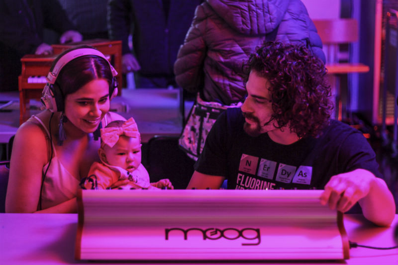Photograph of family playing a Moog synth at the 2018 Ann Arbor Synth Expo
