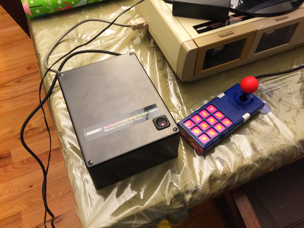 My power supply next to a customized original ColecoVision controller for size comparison. Despite a scratch near the top rear of the power supply, I'm quite happy with how it turned out.