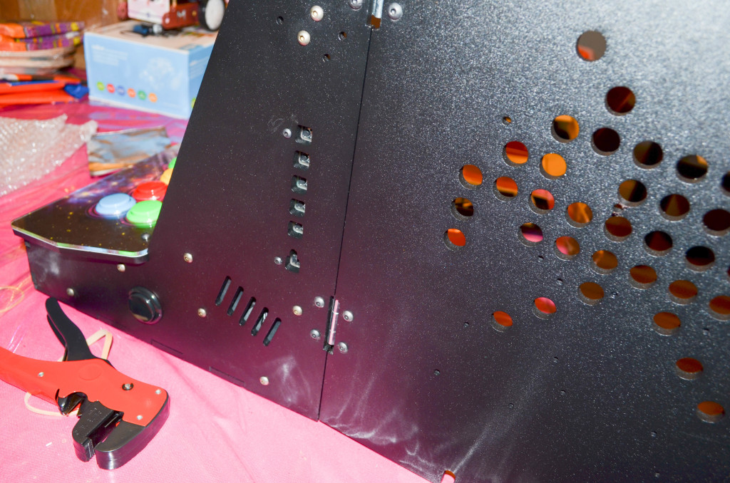 The LCD panel's control panel lines up with the holes on the outside of the cabinet.