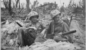 In July 1944 on Peleliu, Marine Pvt. 1st Class Douglas Lightheart (right, holding a 30-caliber machine gun), paused for a smoke. (DoD photo)