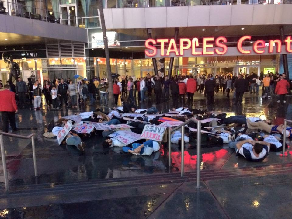 Despite the rain, demonstrators collapsed to the ground in the sudden-death act, as thousands of people exited the Staples Center following a Los Angeles Lakers game.