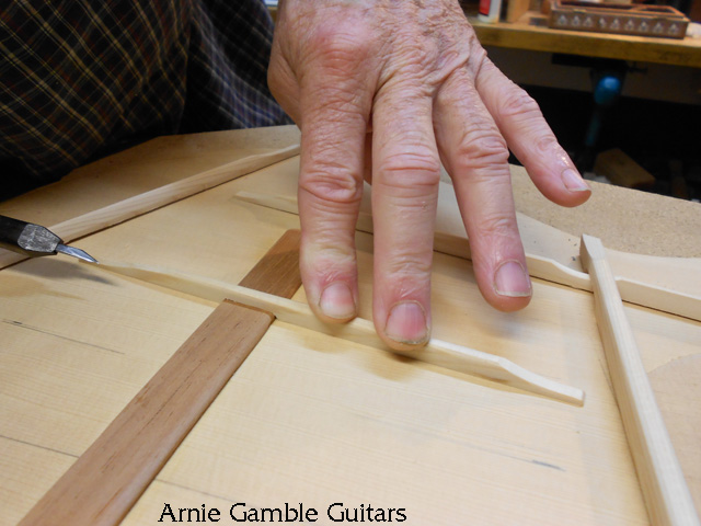 Fitting the bracing the top of the guitar.