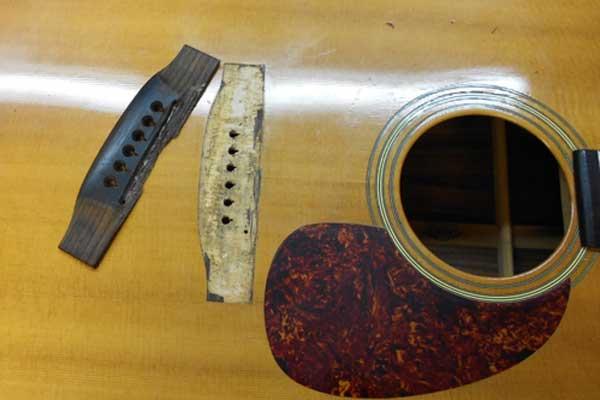 Arnie Gamble reglues the bridge on a Martin guitar.