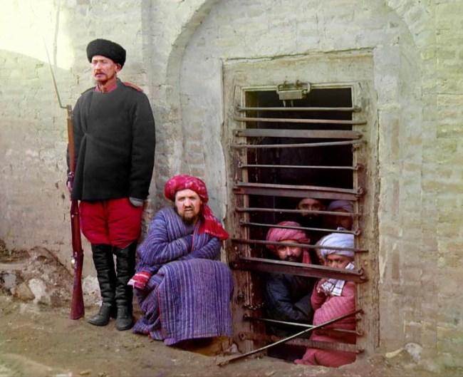 Więźniowie wyglądają przez okno zindanu, obok strażnik w rosyjskim mundurze i uzbrojeniu.