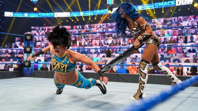 Sasha Banks hits Bayley with a chair