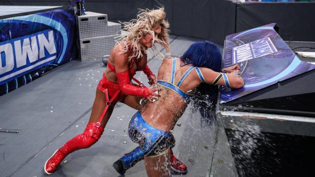 Carmella smashes a bottle of Sasha Banks' back