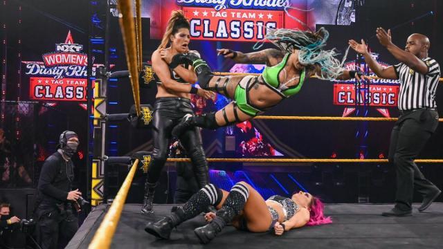 Dakota Kai lays on the mat as Kayden Carter dropkicks Raquel Gonzalez in the corner
