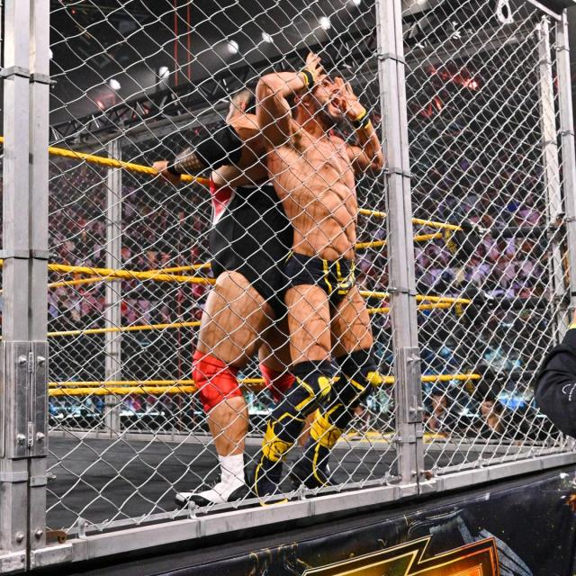 Bronson Reed squishes Johnny Gargano against the cell