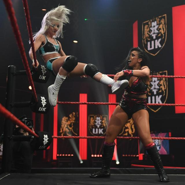 Xia Brookside kicks out at Amale from the top turnbuckle