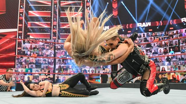 Rhea Ripley drags Charlotte Flair off Nikki Cross and Riptides her.