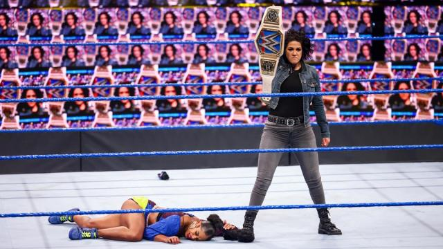 Bayley stands over Bianca Belair holding the title in a ThunderDome full of Bayleys