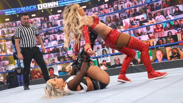 Liv Morgan with her feet in Carmella's back