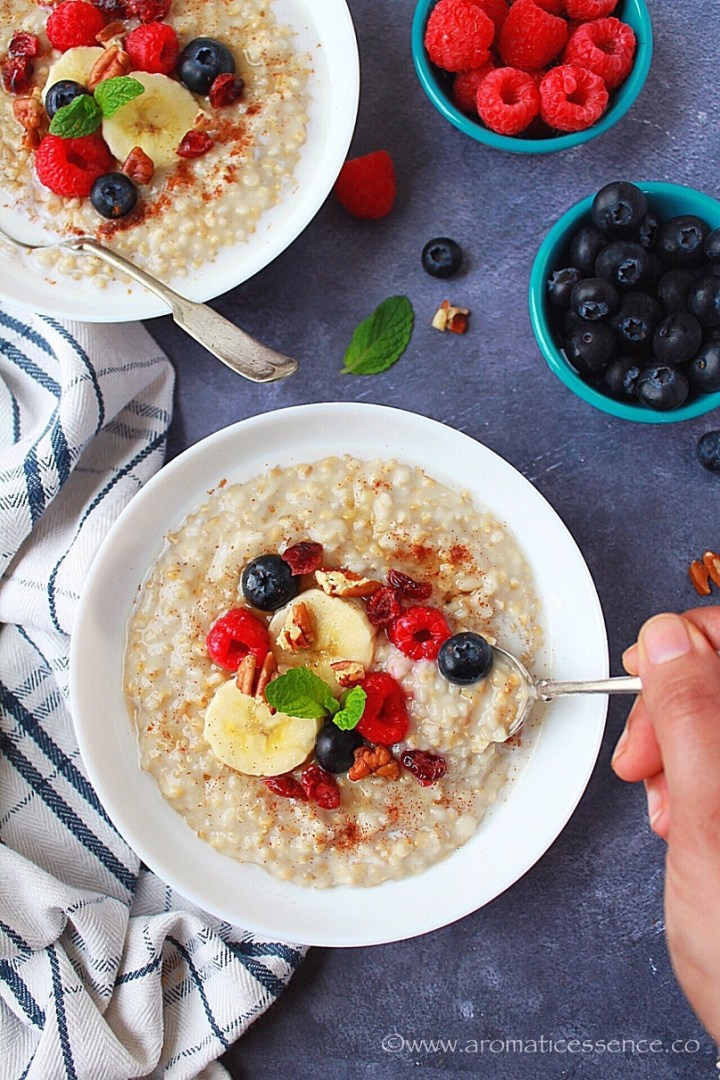 Steel Cut Oats in a white bowl topped with berries, banana slices, and chopped pecans