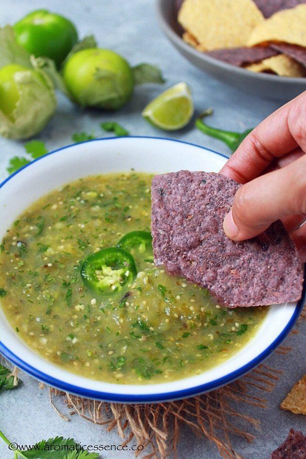 Dipping blue corn tortilla in roasted tomatillo salsa.