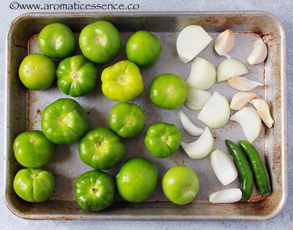 Tomatillos, garlic, serrano peppers and onion on a baking sheet.