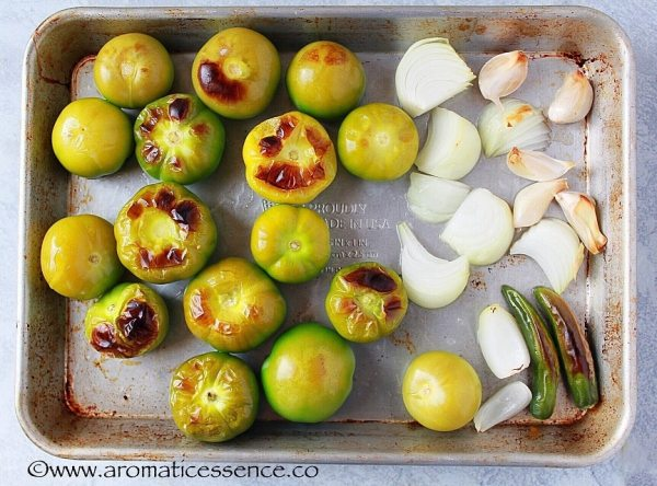 Broiled tomatillos, garlic, serrano peppers and onion on a baking sheet.