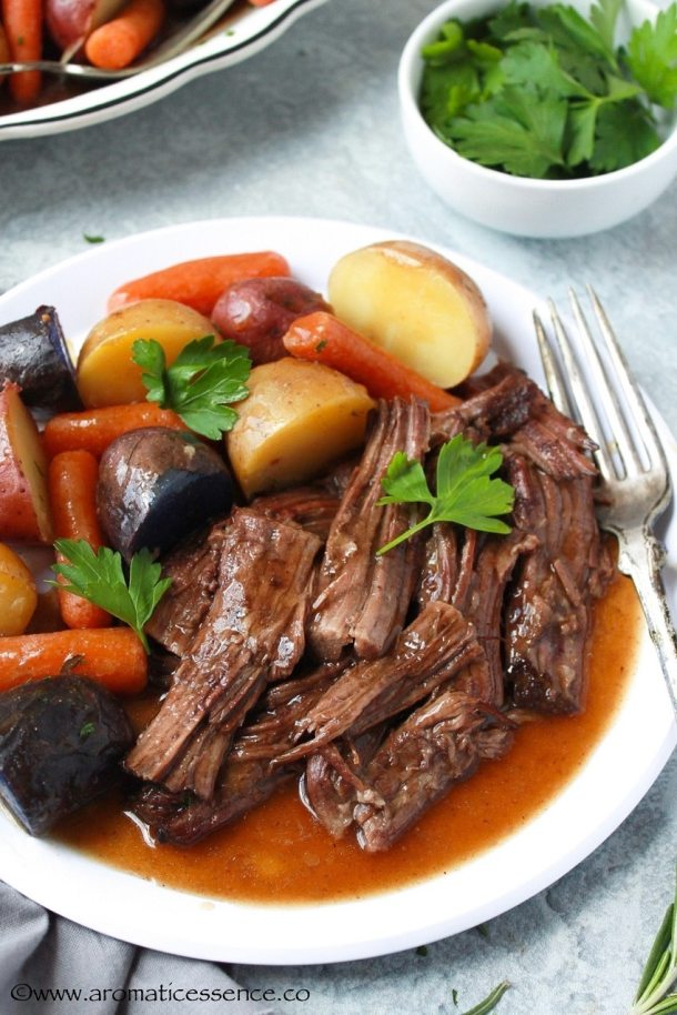 Shredded pot roast with veggies served in a white plate