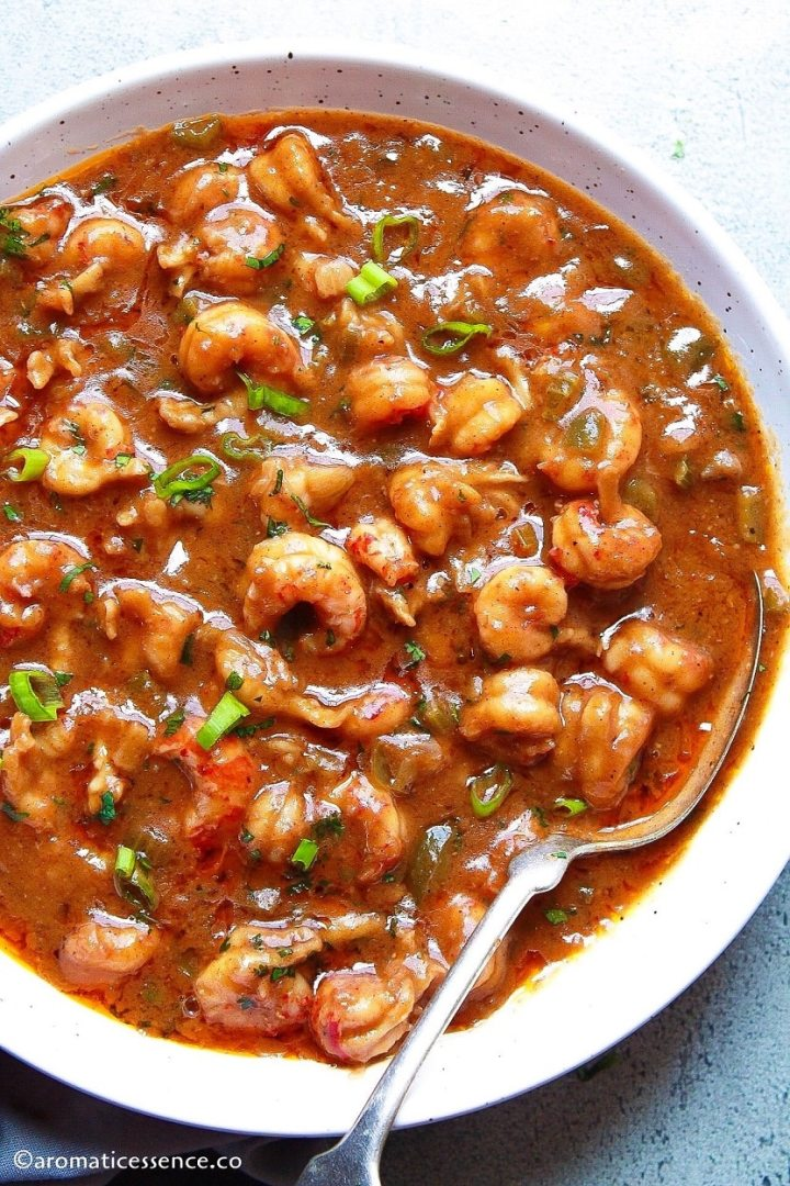 Cajun crawfish etouffee served in a white speckled shallow bowl