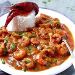 Crawfish etouffee served with a mound of rice on a white plate
