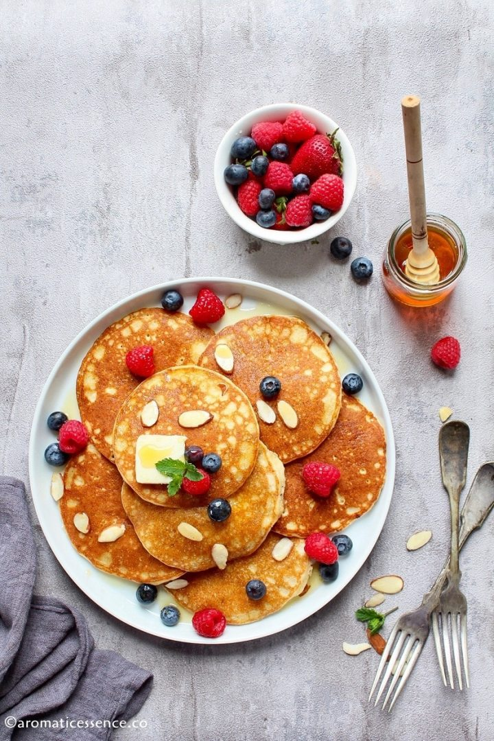 Almond pancakes topped with syrup, butter, and fresh berries