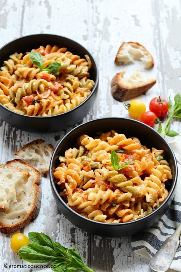 Feta pasta served in two black bowls along with crusty bread