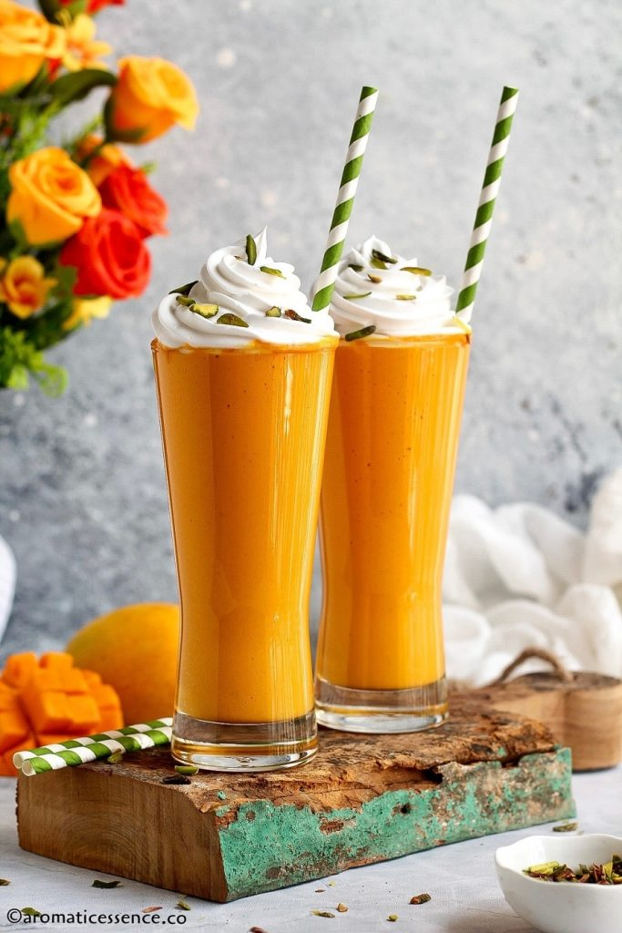 Mango shake topped with whipped cream and slivered pistachios