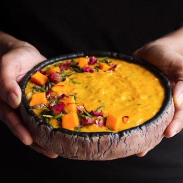 Hands holding a bowl of mango kheer