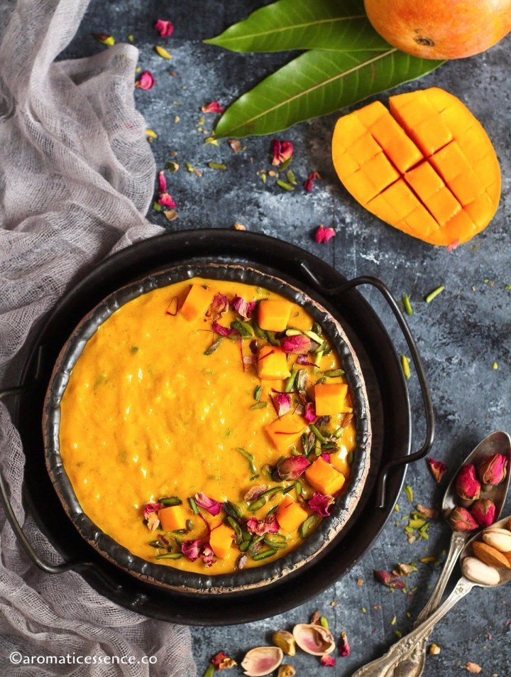 Overhead shot of Indian mango rice pudding with mangoes and mango leaves in the background