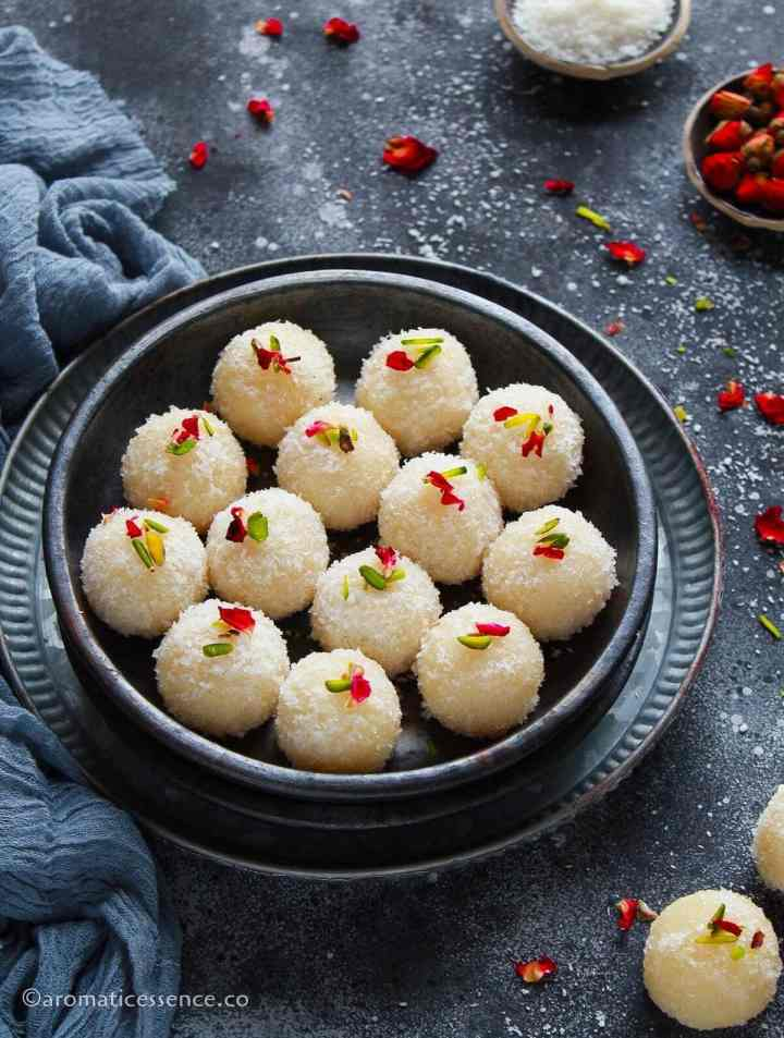 Coconut ladoo served in a black shallow bowl