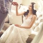 美しい花嫁の画像です。花婿がソファから立ち上がる花嫁の手をとっています