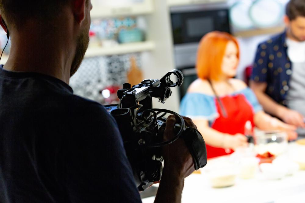 Tecnico con videocamera che riprende una presentazione di cucina