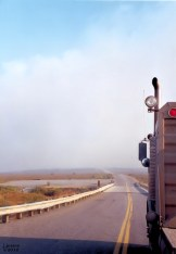 Truck driving into wild fire smoke